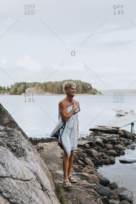 Smiling woman wrapped in towel at sea