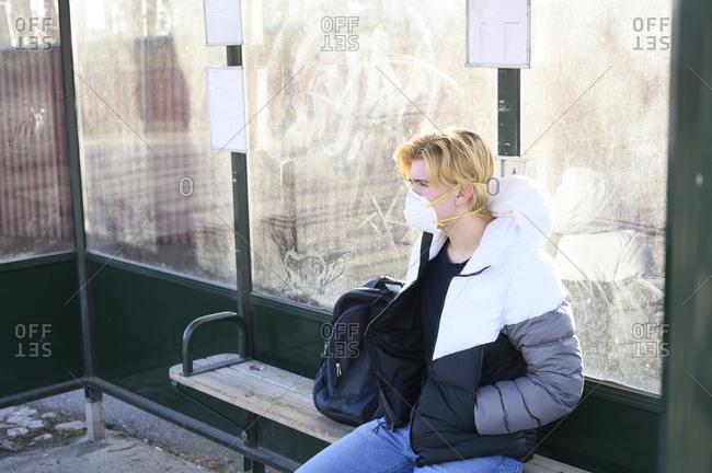 Teenage boy waiting on bus stop