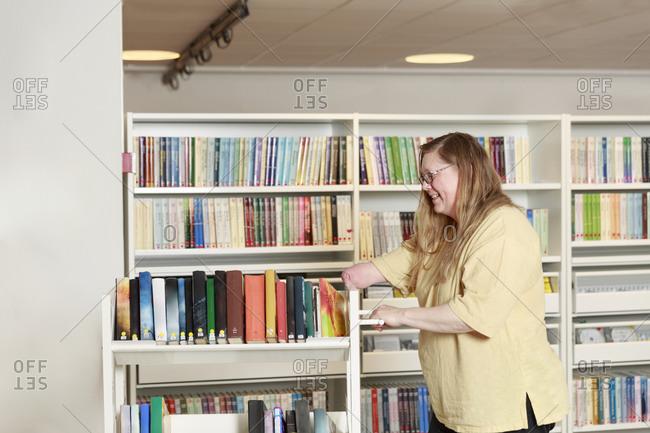 Librarian pushing book trolley forward. Detailed shot.