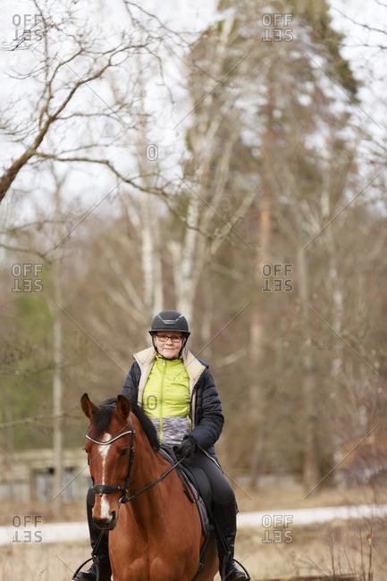 Smiling woman horseback riding. Detailed shot.