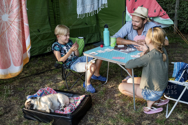 Father with children playing cards front of tent