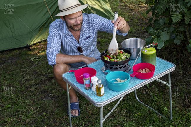 Man preparing food while camping. Detailed shot.