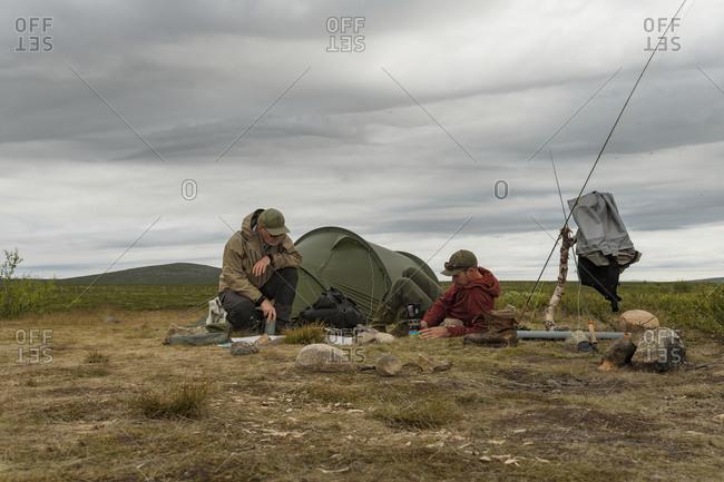 Men relaxing in front of tent