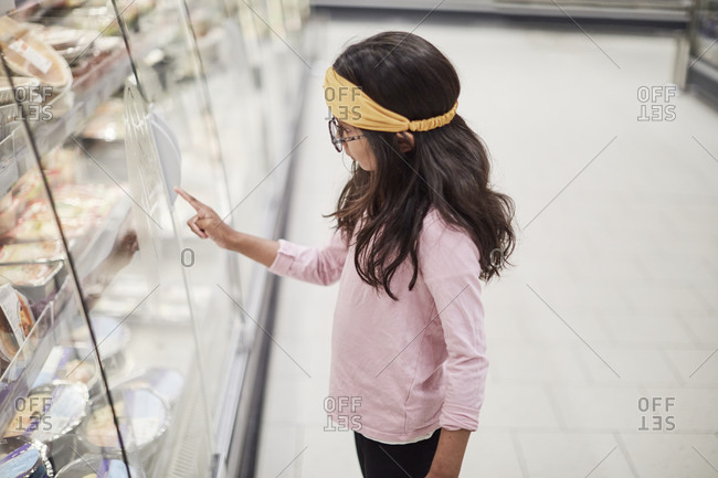 Girl looking at shelves in supermarket