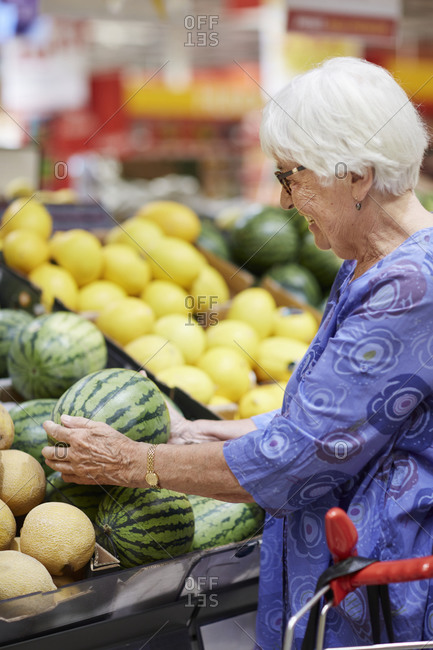 Senior choosing watermelon in supermarket. Detailed shot.