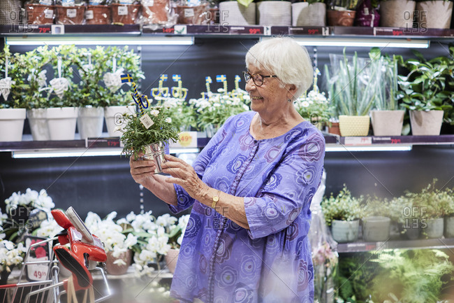 Woman choosing potted plants in shop