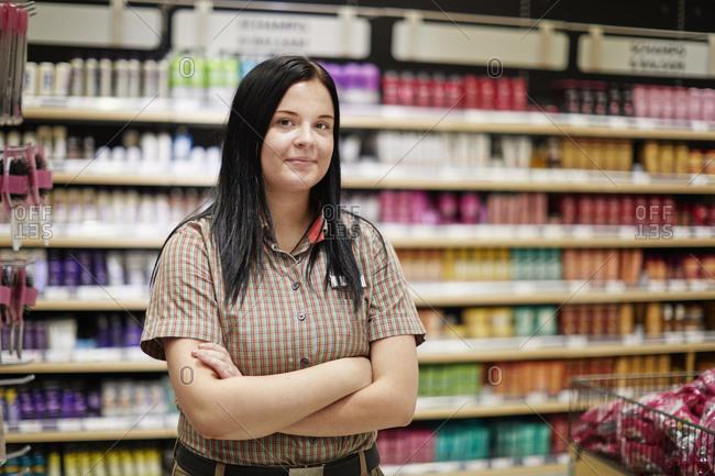 Female shop assistant in supermarket. Detailed shot.