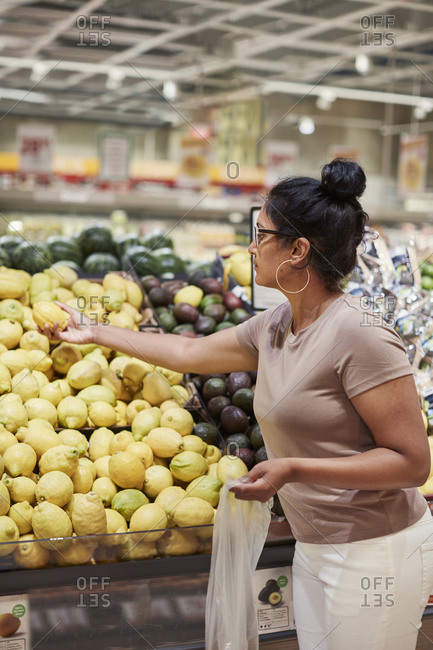 Woman choosing lemon in supermarket. Detailed shot.