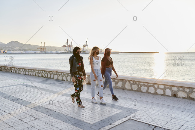 Group of diverse young female friends wearing protective face masks walking together along an ocean promenade at dusk