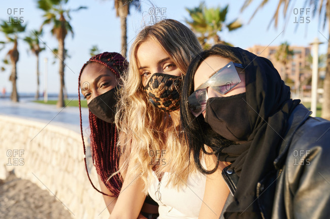 Diverse group of young female friends in face masks smiling from under face mask while sitting in a city park