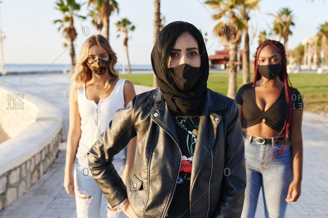 Young Muslim woman and two friends wearing face masks standing together on a path through a park