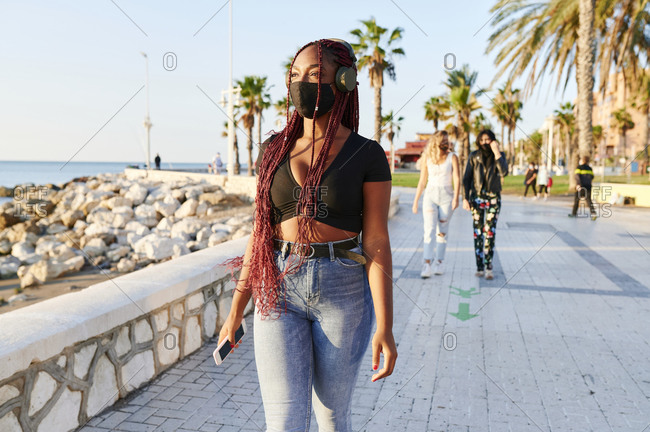 Young African woman wearing a protective face mask listening to music on headphones while practicing physical distancing in a park