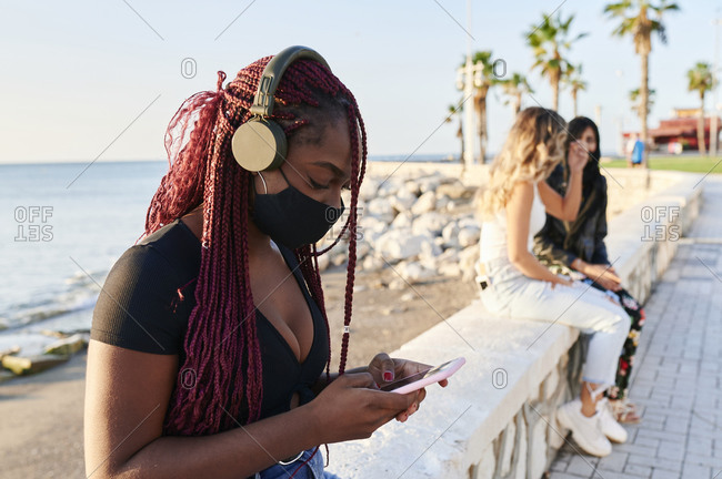 Young African woman wearing a protective face mask listening to music on headphones while physical distancing by the ocean
