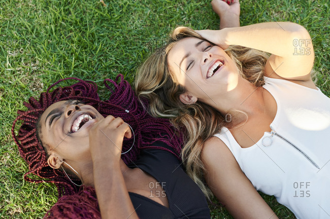 Two diverse young female friends laughing while lying on some grass in a park on a sunny afternoon