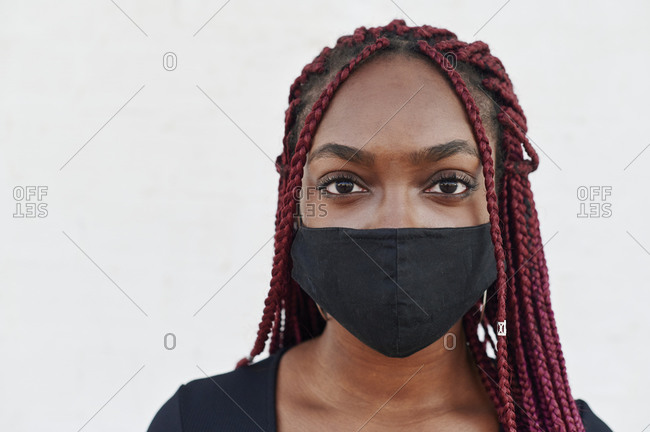Young African woman standing outside in front of a brick wall wearing a protective face mask