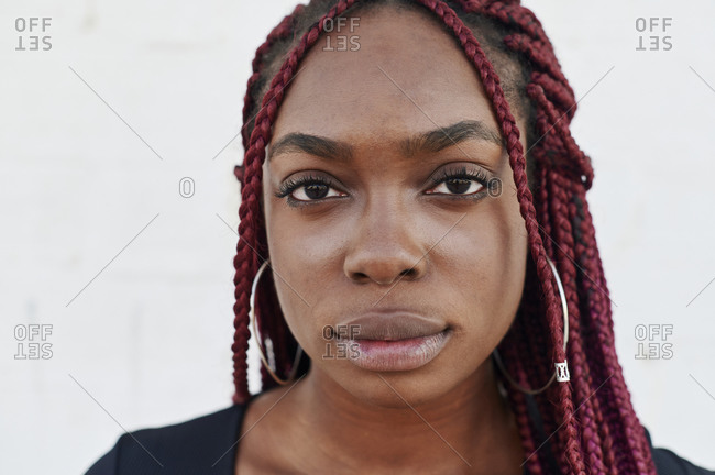 Confident young African woman with colorful braided hair standing in front of a brick walk