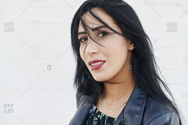 Confident young woman with black hair and  face piercings standing outside in front of a brick walk