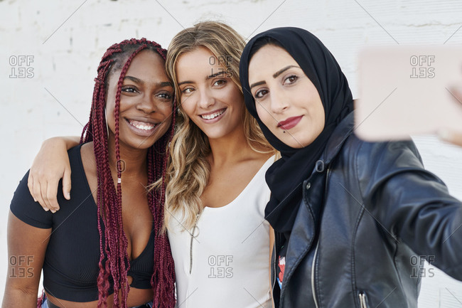 Three diverse young woman smiling and taking selfies together while standing outside