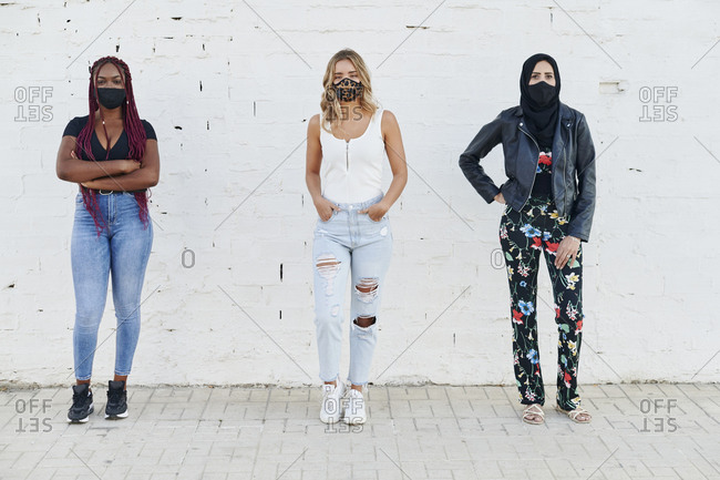 Three diverse young woman wearing protective face masks practicing physical distancing outside in front of a brick wall