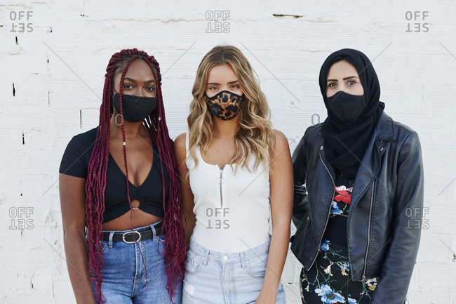 Three diverse young woman wearing protective face masks standing together outside in front of a brick wall