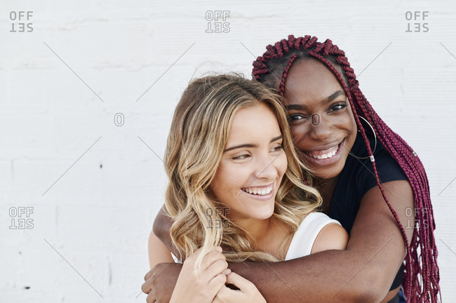Laughing young African woman hugging her smiling friend from behind while hanging out together outside