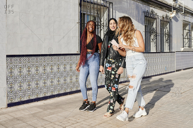 Diverse group of laughing young female friends walking together along a sidewalk in the city on a sunny afternoon