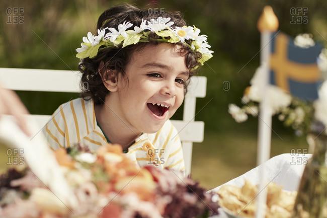 Happy boy wearing flower wreath. Detailed shot.