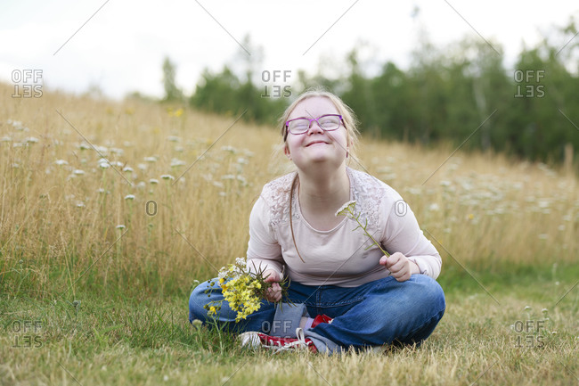 Smiling girl on meadow holding wildflowers