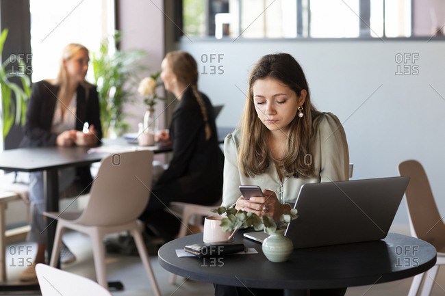 Businesswoman in cafe checking cell phone