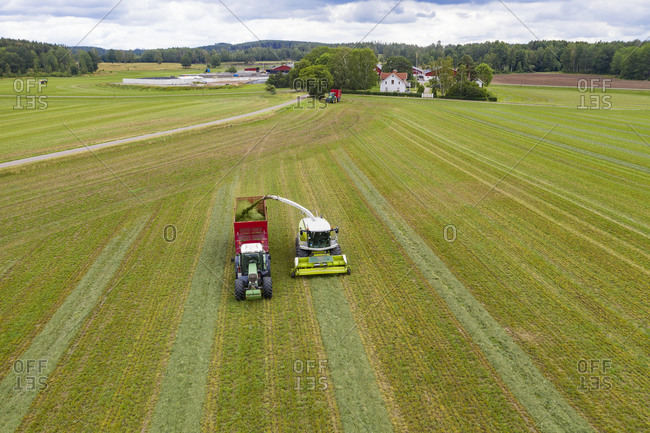Harvester and tractor on field. Detailed shot.
