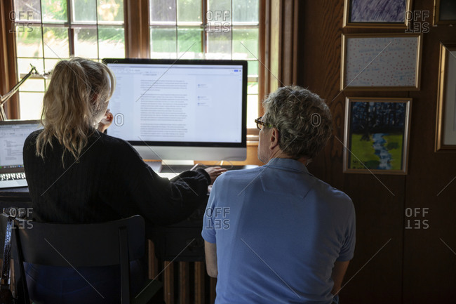 Father with adult daughter looking at computer screen