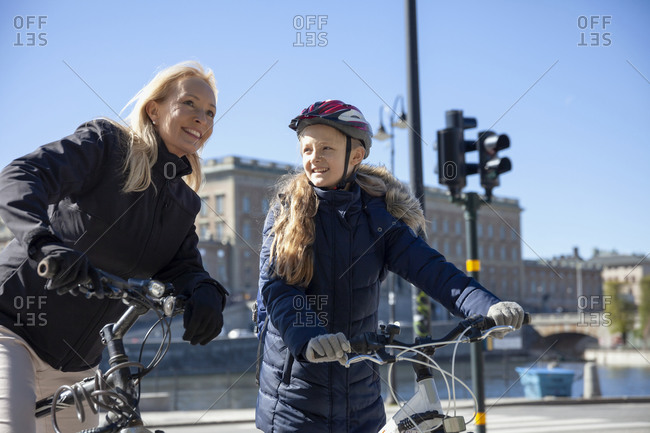 Mother and daughter cycling together. Detailed shot.