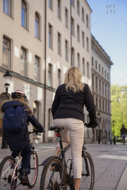 Mother and daughter cycling in city
