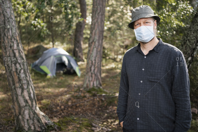 Man wearing face mask looking at camera, tent on background