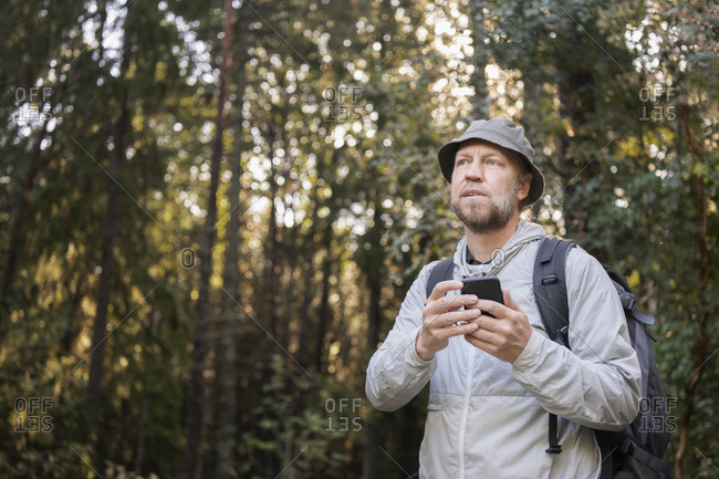 Hiker using cell phone. Detailed shot.