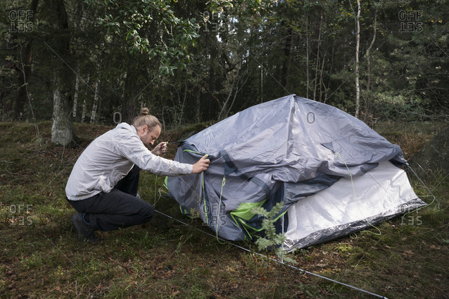 Man wild camping, setting up tent