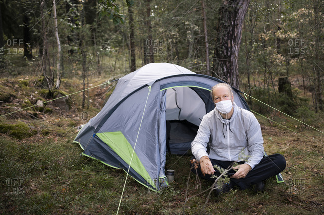 Man wearing face mask sitting in front of tent