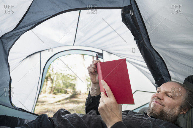 Man reading book in tent. Detailed shot.