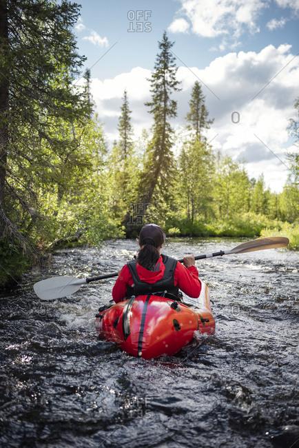 Woman kayaking on river. Detailed shot.