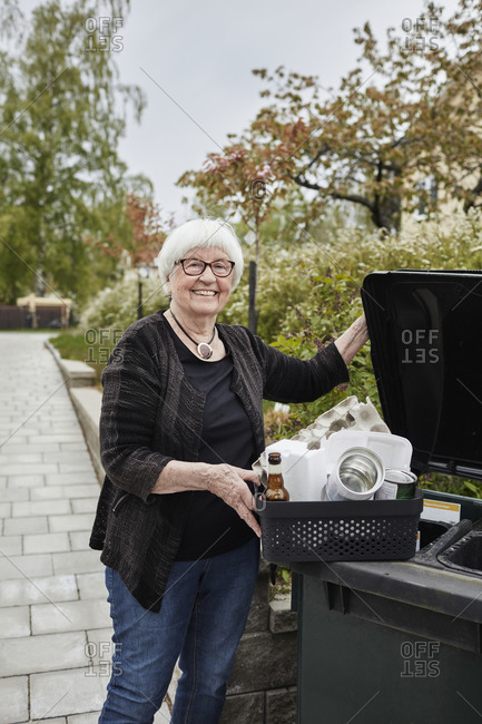 Smiling senior woman carrying recycling rubbish