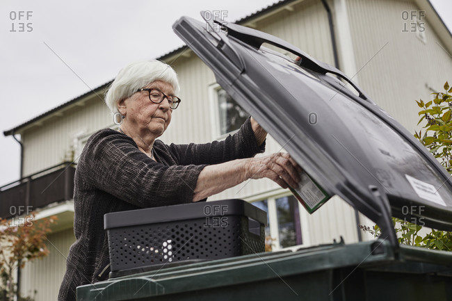 Woman putting rubbish into bin. Detailed shot.