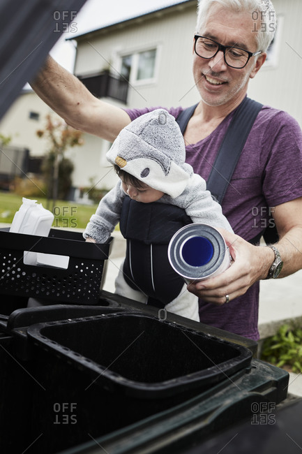 Smiling mature man with baby putting rubbish into bin