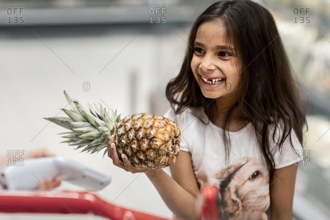 Smiling girl holding pineapple. Detailed shot.