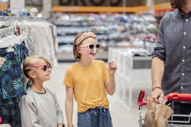 Smiling girls trying sunglasses in shop