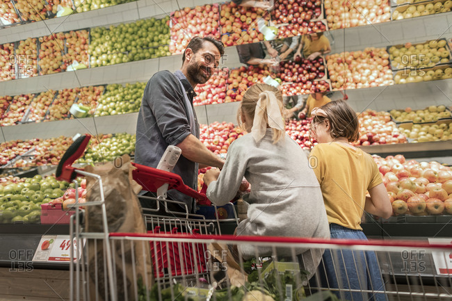 Father with daughters doing shopping in supermarket