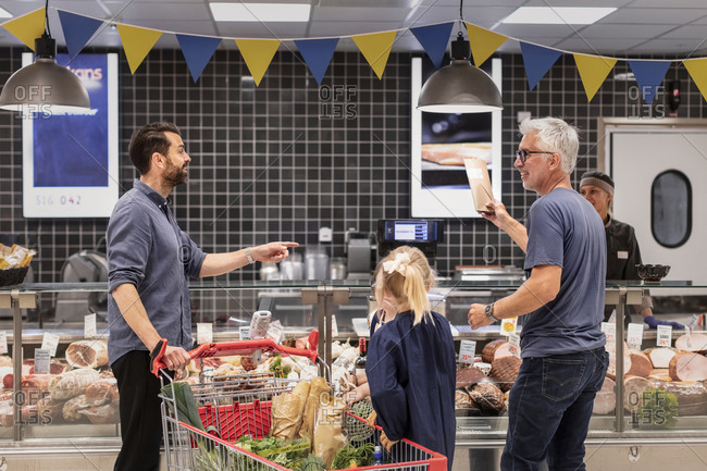 Customers talking in supermarket. Detailed shot.