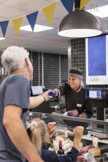 Customer at deli counter in supermarket
