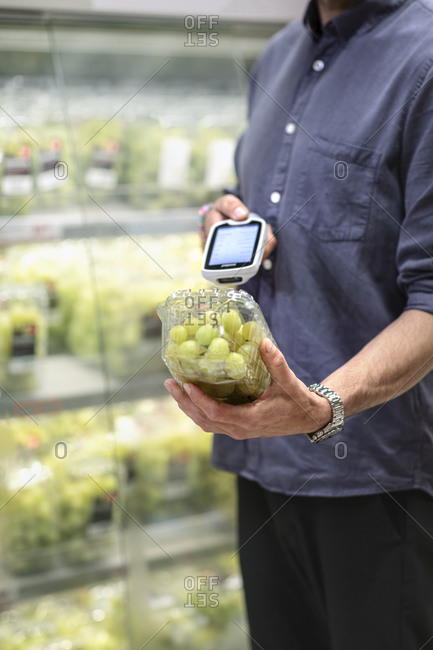 Man in supermarket scanning pack of grapes