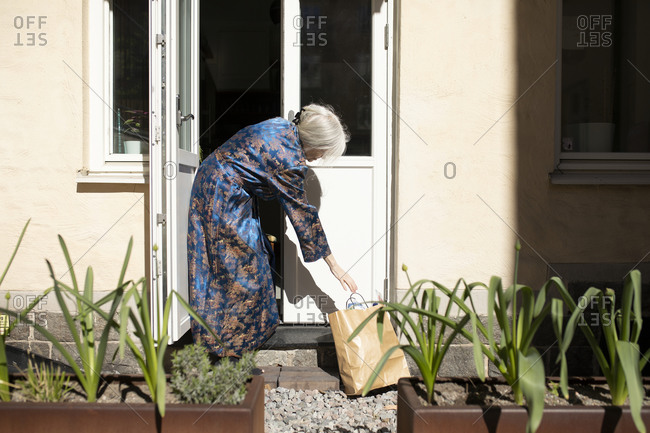 Woman reaching for paper bag in front of house