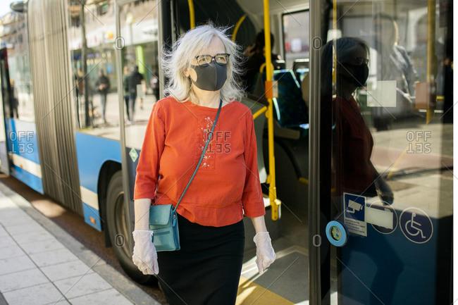 Woman wearing face mask standing near bus